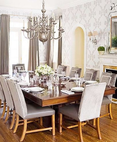 Modern-traditional dining room with grey upholstered chairs with white trim, silver chandelier, white fireplace and arched entryways