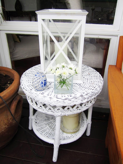 White hurricane lantern on wicker side table