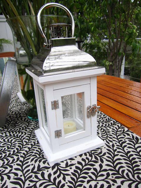 White wood lantern on an outdoor dining table