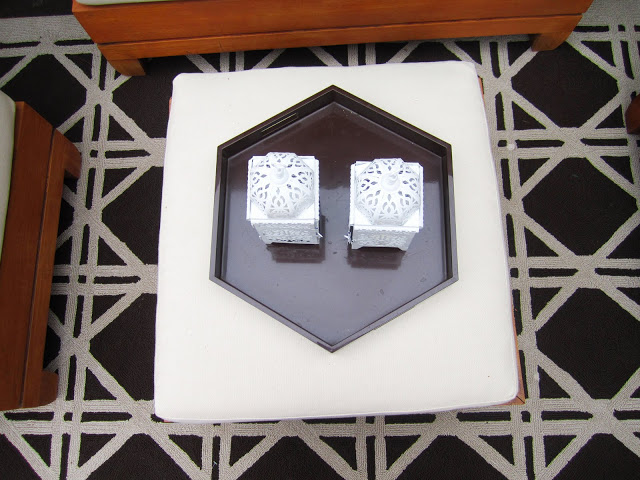 Shiny brown hexagon lacquer tray on white ottoman with two white Moroccan lanterns