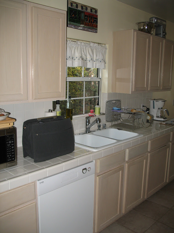 Narrow kitchen with old cabinets and tiled countertops