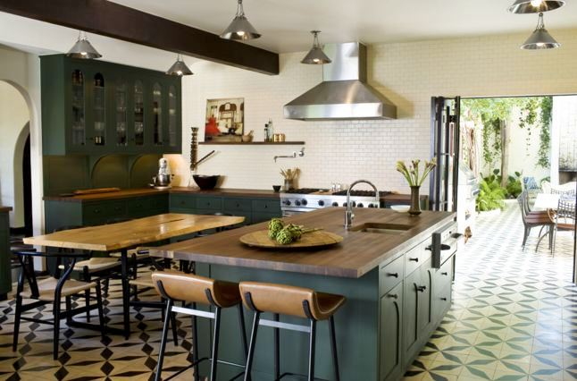 Eat in kitchen with mosaic tile floor, white subway tile backsplash, dark green cabinets and matching island with butcher block top