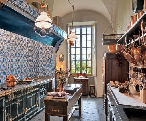 Kitchen in Château du Sailhant with copper pots and pans, La Cornue range and terra-cotta tiles