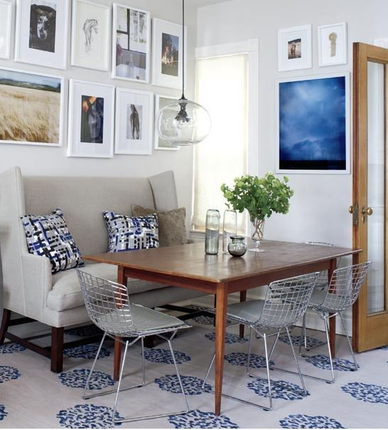 Small dining room with banquet style love seat, Bertoia chairs, a mid-century modern dining table, a simple glass pendant light, and a Madeline Weinrib rug