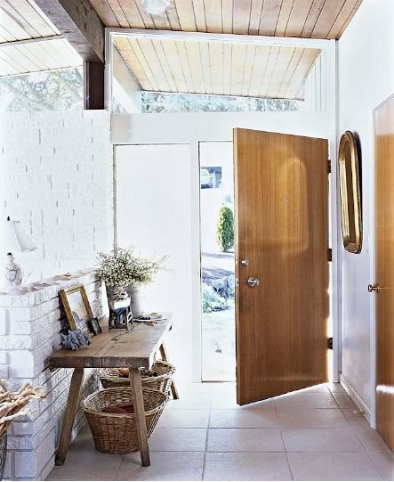 Rustic foyer with unadorned wood door and plank ceiling and white washed brick