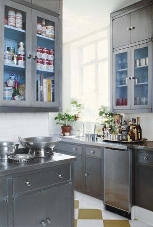 Kitchen with grey cabinets and drawers, the upper cabinets have glass doors with light blue interiors, white subway tile backsplash and gold and white checkerboard floor