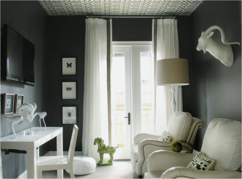 Dark grey TV room with large glass door with long sheer curtains, wallpapered ceiling, white leather armchairs with nail head trim, a white desk, wall mounted TV and a white ram head