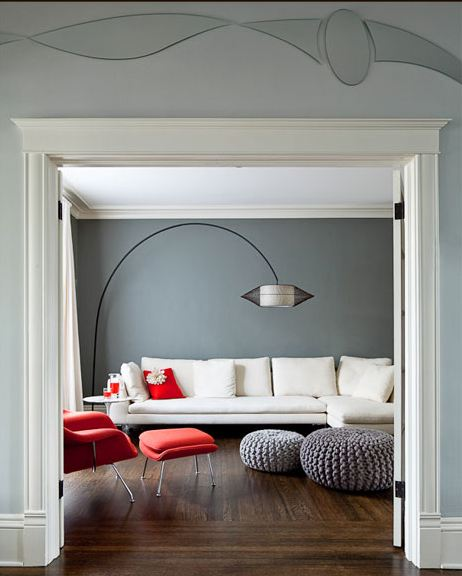 Grey living room with wood floor, grey knit poufs, white sectional sofa, red Womb Chair with matching ottoman and black arched lamp