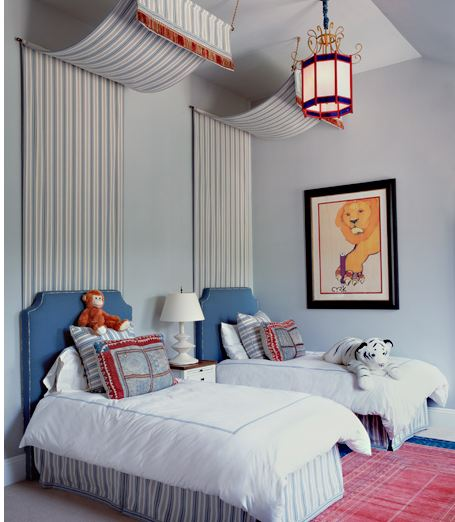 Bedroom with two twin beds with striped canopies and blue upholstered headboards, a red rug and a colorful lantern