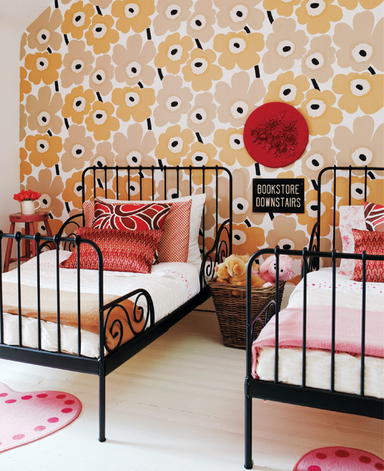 Bedroom with Marimekko wallpaper, two twin beds with black iron frames and white bedding with brightly colored pillows, and a light wood flor