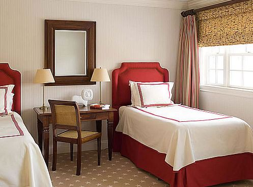 Bedroom with two twin beds red upholstered headboard, white bedding with red trim, instead of a nightstand, between the beds is a wood desk with a wood chair with woven seat and back, and striped curtains