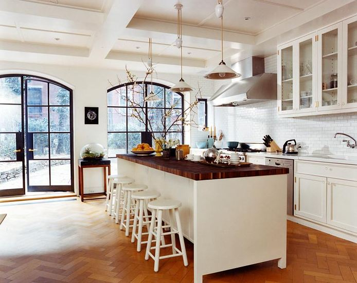 White open kitchen with butcher block countertop, herringbone wood floor, huge arched multi-paned glass doors and window, two white pendant lights, white subway tile backplash, white drawers and cabinets and a white island surrounded by white stools