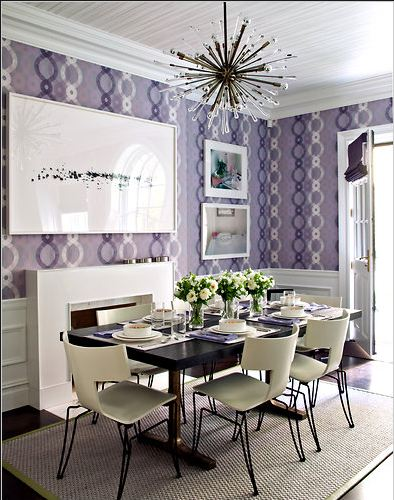 Dining room with lavender wallpaper, white fireplace, wood floor, sisal rug and Sputnik chandelier