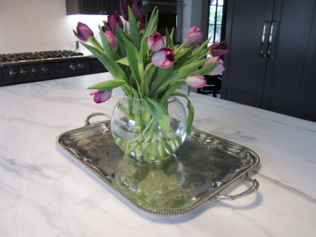 Silver Sheffield tray with a glass vase holding purple tulips on a kitchen island with marble counter top