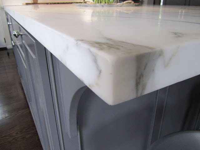 Corner of a large grey island topped with Calacatta gold marble in a kitchen