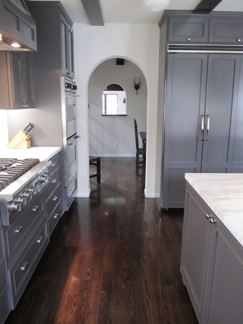 Arched entry way out of a kitchen with dark grey cabinets and drawers, marble counter tops, wood floor, and a large island with a marble top
