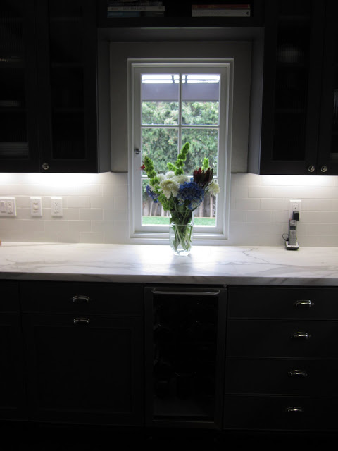 Kitchen with grey cabinets and drawers, marble counter top, casement window and a flower arragement