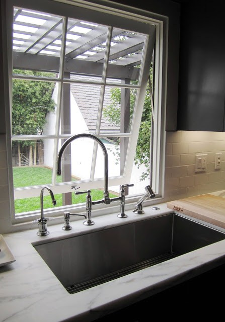 Kitchen with casement picture window, arched Kohler metal faucet and fittings, and marble counter top