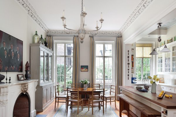 Open kitchen and dining area with high ceilings, carved moldings, grey walls, a fireplace, a grey china cabinet, white cabinets and drawers and a butcher block topped island with wood bench style seating