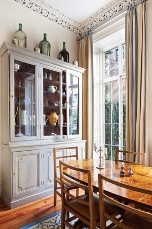 Grey dining room with high ceilings, carved moldings, a grey china cabinet, large windows and a wood table surrounded by matching chairs