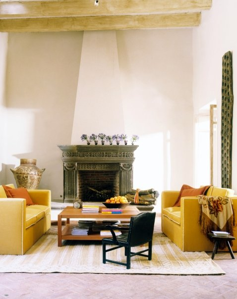 Living room with large dueling yellow upholstered sofas, a wood coffee table, visible natural wood beams and a carved fireplace