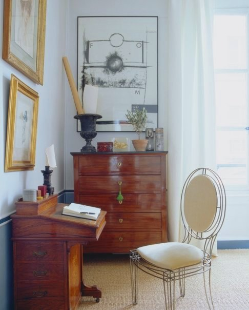 Room in a Paris apartment with a wood writing desk with a wire chair and white cushions and chest of drawers, a sisal rug and large french doors