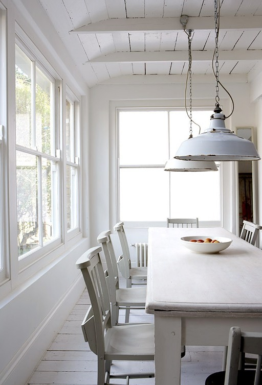 White rustic dining room with white washed floors, tables and chairs, exposed beams and white dome style pendant lights