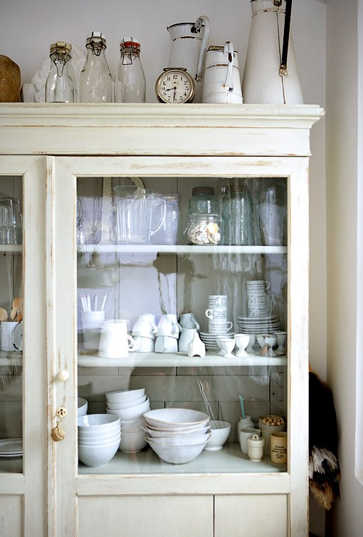White china cabinet in a white rustic eat in kitchen