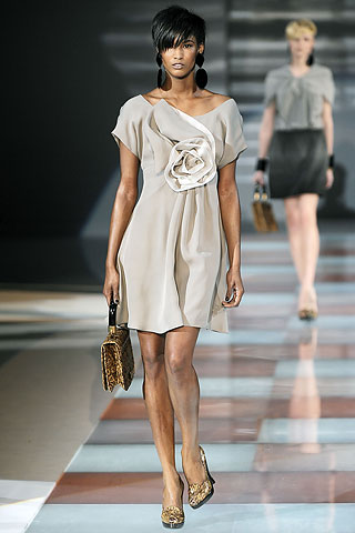 Model from Emporio Armani's Fall Ready-to-Wear 2010 fashion show wearing a grey dress with a large flower