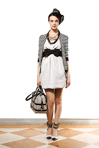 model from Moschino Cheap & Chic's Resort 2011 Ready-to-Wear collection in a white dress with a large black belt with a bow, striped cardigan, heels and a black pillbox hat