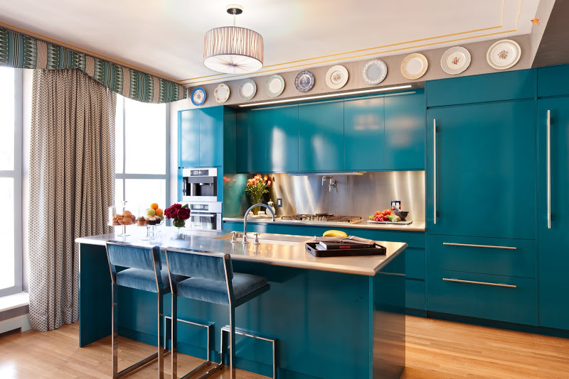 Blue kitchen that Zac Posen collaborated on with a wood floor, cabinets and drawers with long silver pulls, decorative plates, a drum pendant light, large windows with grey floor length curtains, at the island there are two bar chairs with blue velvet seats and backs