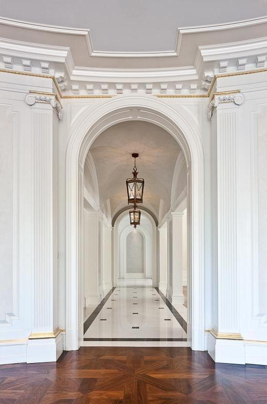 Hallway with wood floor, Greek columns, arched entryway, black and white tile floor, moulded detailing and a coffered ceiling