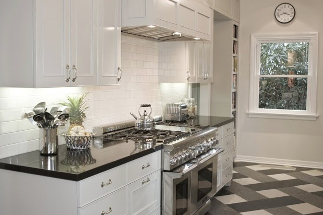 Kitchen after it's Tom Newman inspired makeover with a plaid tile floor, black counter top, white cabinets, white subway tile backsplash and stainless appliances