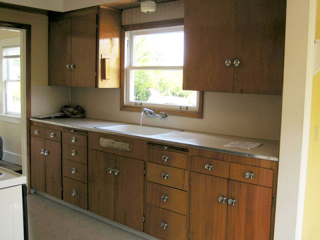 Kitchen before it's Tom Newman inspired makeover with wood drawers and cabinets and light brown title floor
