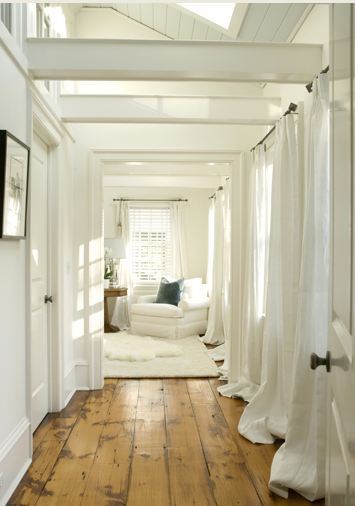 Hallway with natural wood floor leading to a white bedroom
