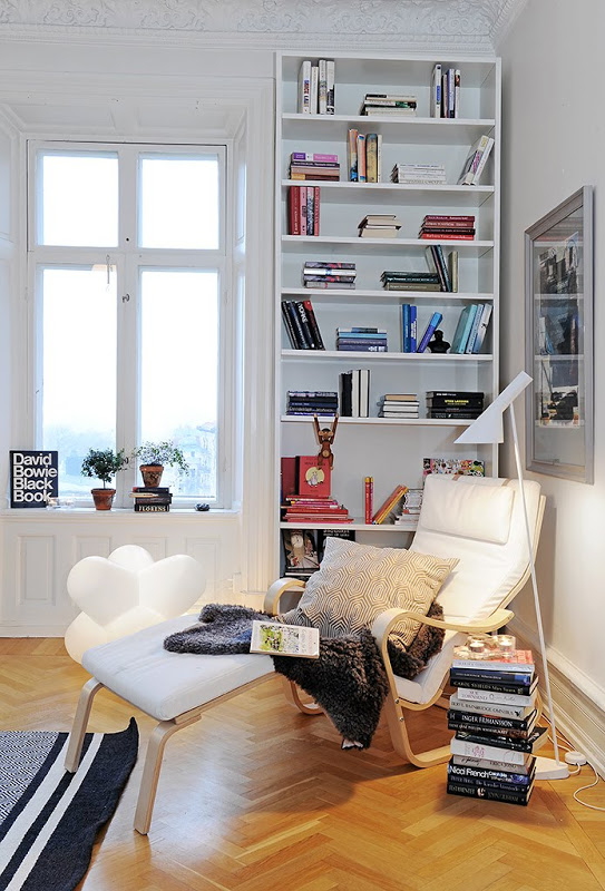 Close up of the lounge chair and stack of books in a home office in a Swedish apartment with  herringbone wood floor, carved crown molding, a blue striped rug, built in bookcase