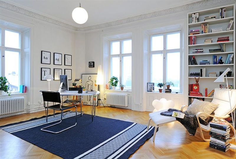 Alternative view of a home office in a Swedish apartment with  herringbone wood floor, carved crown molding, the decorative ceiling medallions, tall paneled doors, metal desk, and chair, a blue striped rug, built in bookcase and a white lounge chair with a stack of books, and a globe light