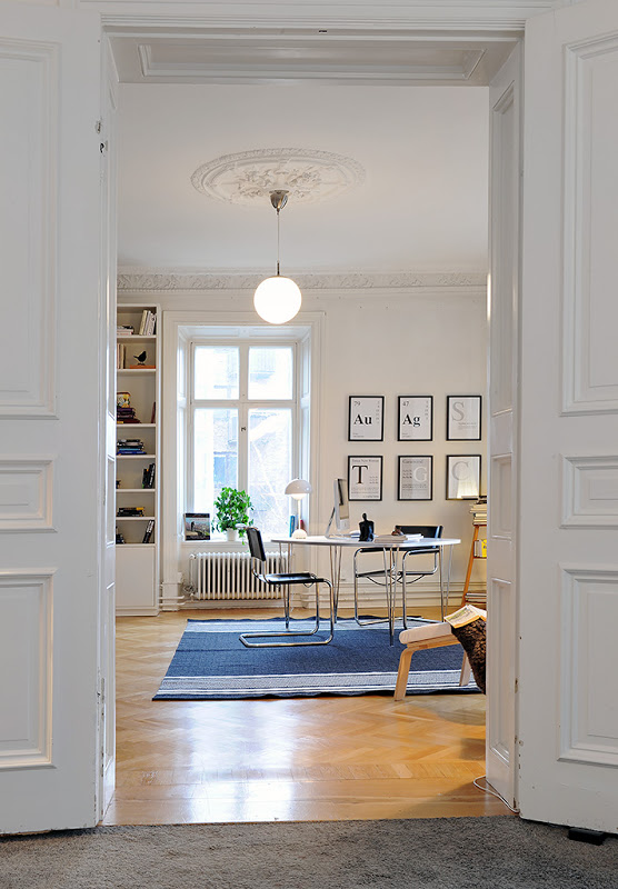 Home office in a Swedish apartment with  herringbone wood floor, carved crown molding, the decorative ceiling medallions, tall paneled doors, metal desk, and chair, a blue striped rug and a globe light