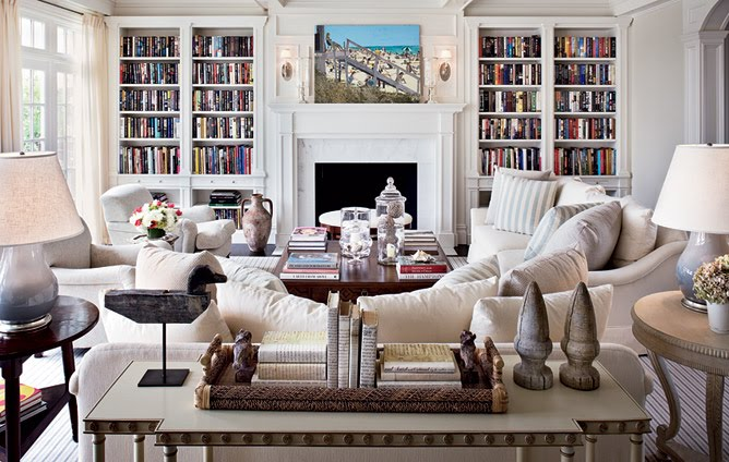 White living room with two sofas, arms chairs, wood side tables, a striped rug, built in bookcases and a fireplace