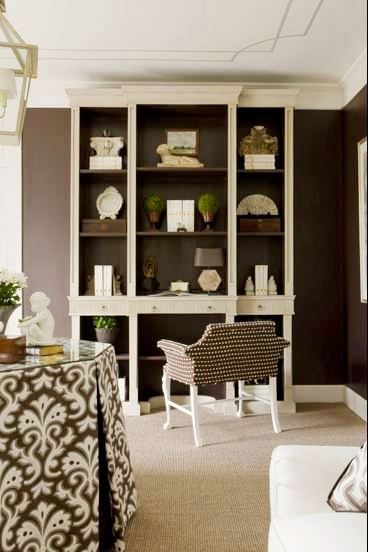 Sitting room with brown walls, grey carpet floor, detail trim painted on the ceiling, built in shelves and a brown polka dot upholstered sette