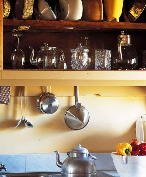 Close up of the stove, the yellow walls, and the yellow shelves with natural wood back