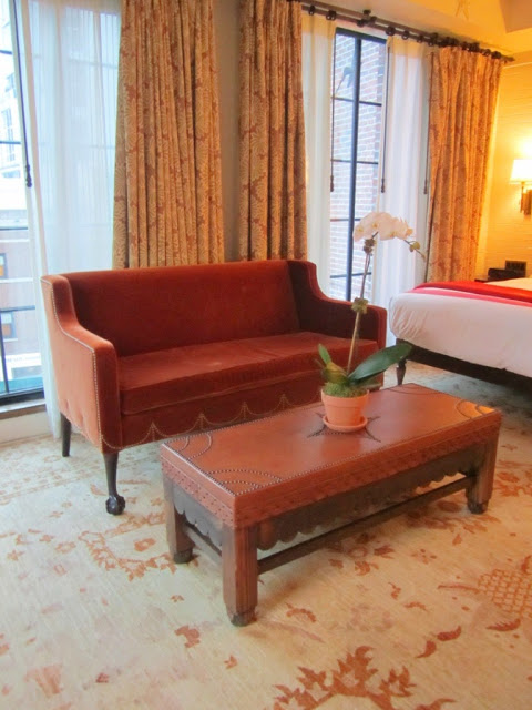 Leather sofa and matching ottoman with nail head trim in at The Bowery Hotel