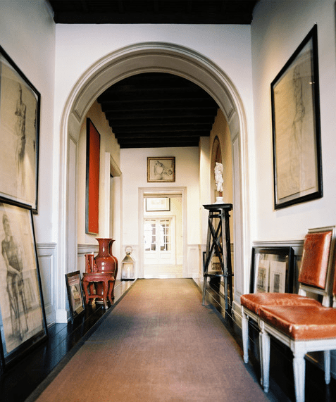 Foyer with arched entryway, dark wood floor, a long rug, two white chairs with leather seats and back and lots of sketches in black frames on the wall