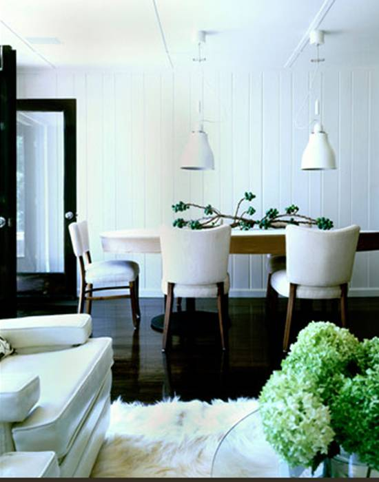 Dining room with dark wood floor, beadboard walls, two white pendant lights, wood chairs with white upholstered seats and backs and a sculptural centerpiece
