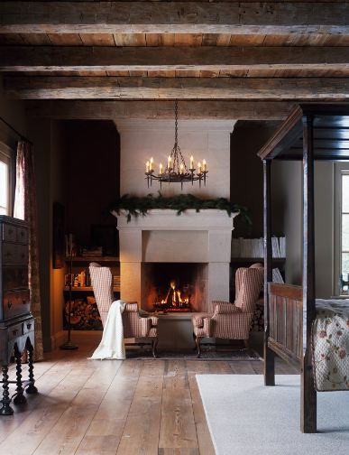 Bedroom with wood floor, exposed beams, a large fireplace with a festive holiday garland