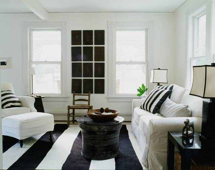 Alternative view of a living room in a cottage with black and white striped rug, white sofa, armchair and ottoman with black and white striped accent pillows, a black coffee table and a fake window