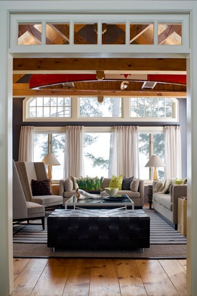 Living room in a cabin with knotty wood floor, a black bench style ottoman, grey sofa and armchairs with high backs