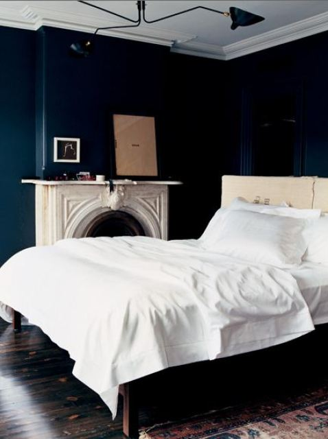 Bedroom with navy walls, a white bed, marble fireplace with a mirror on the mantel, dark wood floor, molded ceiling detail and a Turkish rug