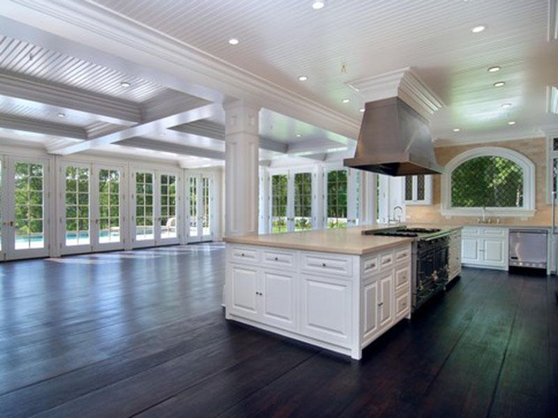 Open kitchen with columns, beadboard ceiling, dark wood floor, marble counter tops and back splash and wrap around French doors and windows