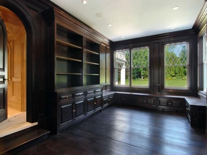 Library with dark stained wood floor and wood paneling and an arched door - SEE THIS HOUSE: A $35 MILLION HAMPTONS HOUSE WHERE WOOD PANELING